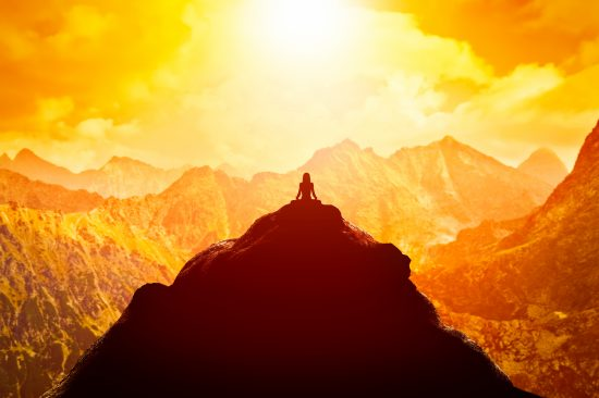 Woman meditating in sitting yoga position on the top of a mountains above clouds at sunset. Zen, meditation, peace